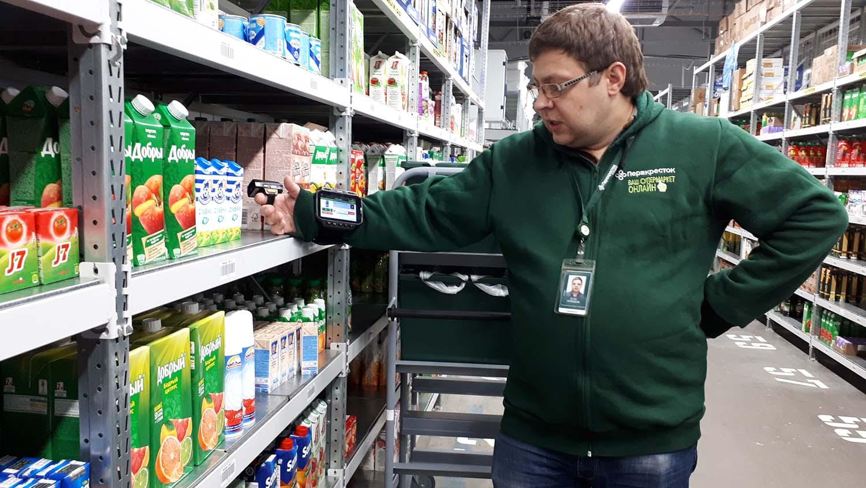 Сборщик сортирует однотипные товары в (ролл-кейджи)